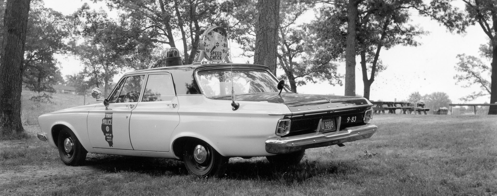 Black and white 1963 Plymouth Savoy with speed check device mounted on the roof.  State Police was part of the Department of Public Safety.